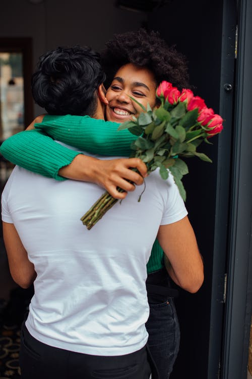 Woman in White T-shirt Holding Bouquet of Flowers