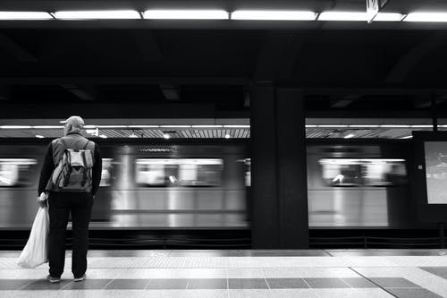 Man in Black Suit Standing Beside Train
