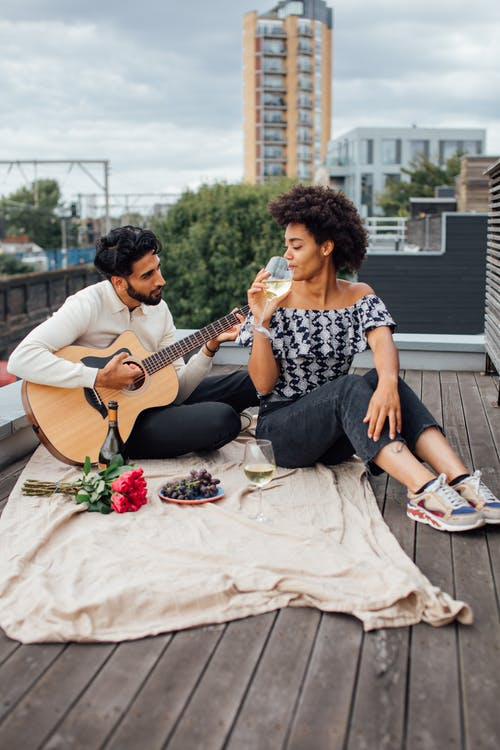 Man and Woman Sitting on Blanket While Playing Guitar