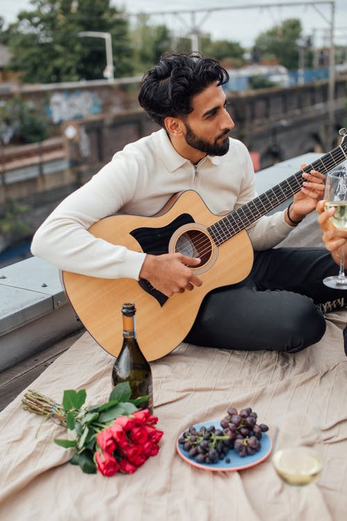 Man in White Long Sleeve Polo Playing Acoustic Guitar