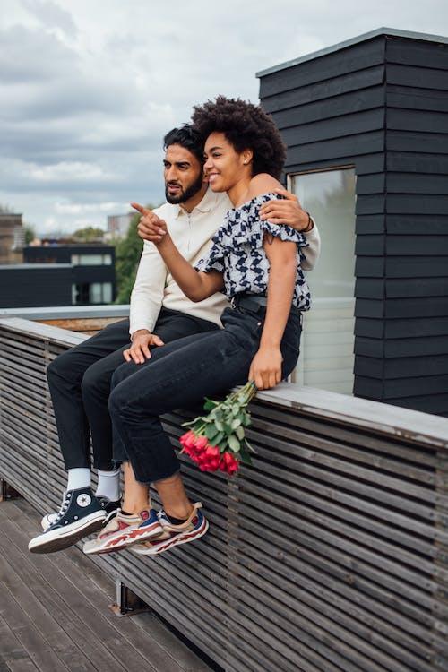 Femme En Chemise Noire Et Blanche Et Pantalon Noir Assis Sur Un Banc En Bois Marron