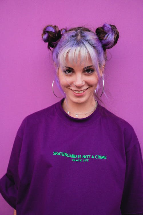 Young happy extraordinary female with dyed hairstyle and earrings looking at camera on purple background