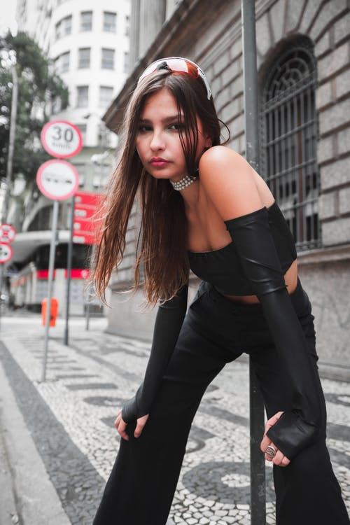 Confident young female wearing trendy black outfit standing on pavement of city and thoughtfully looking at camera