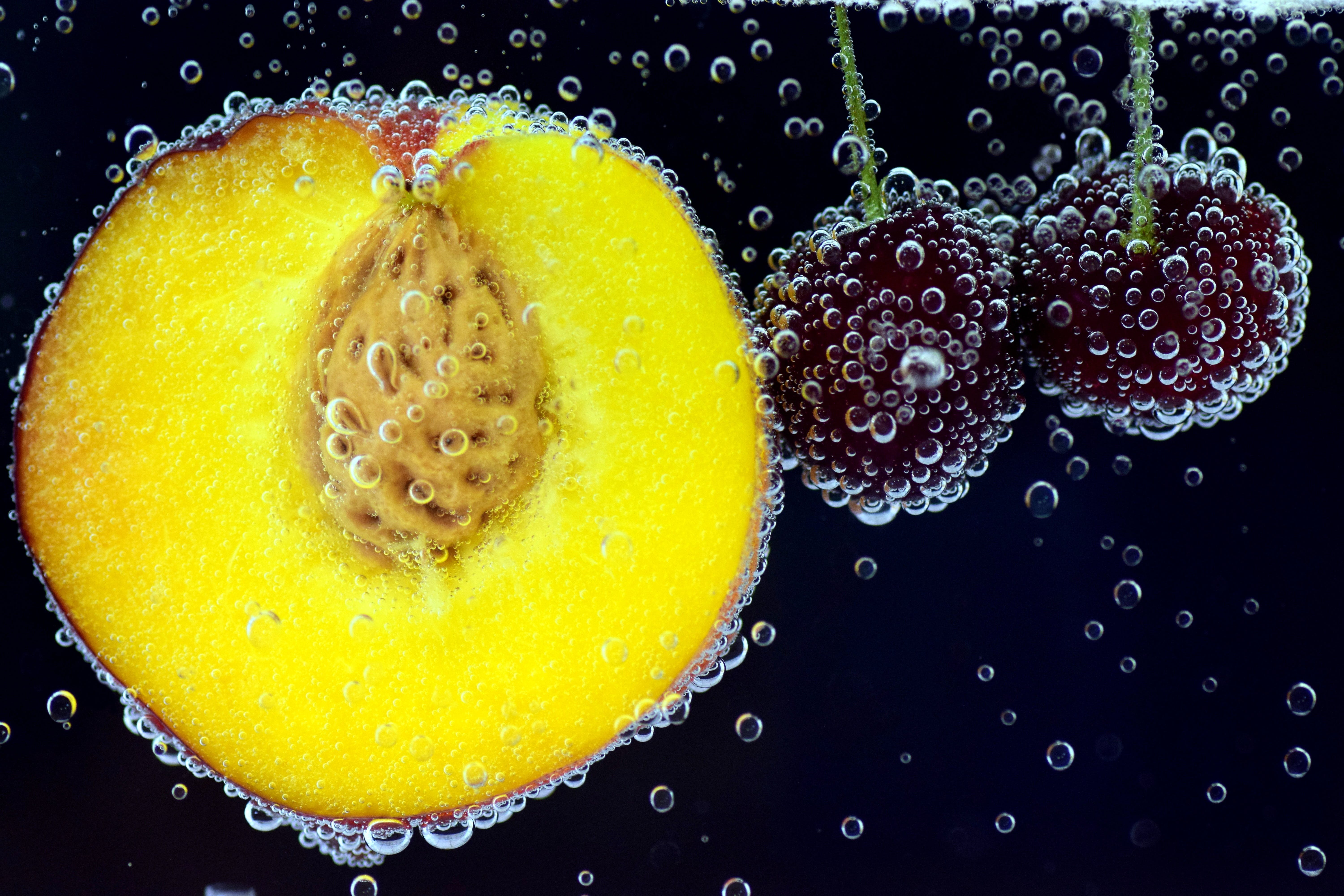 Sliced Fruit and Two Red Fruits in Water