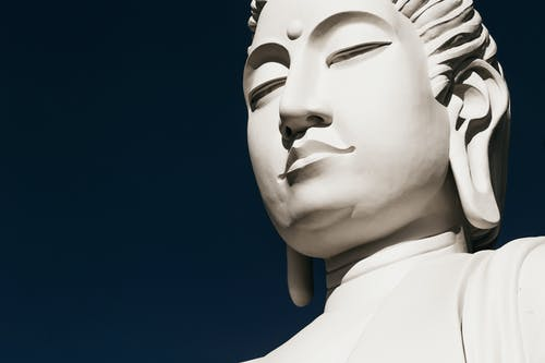 Statue head of Buddha with long earlobes and eyes closed on blue background