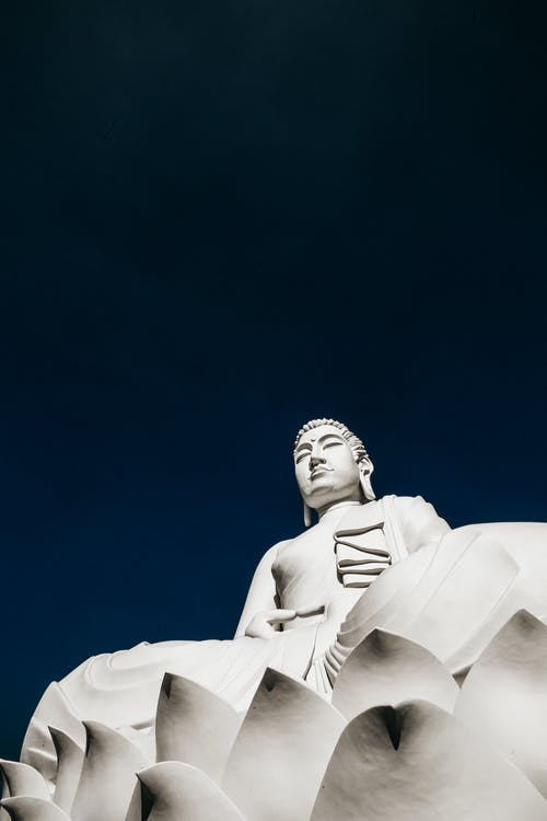 From below of old famous statue of Buddha resting on lotus under clear blue sky