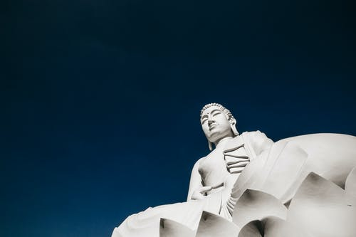 From below of stone religious sculpture with eyes closed sitting peacefully under clear blue sky