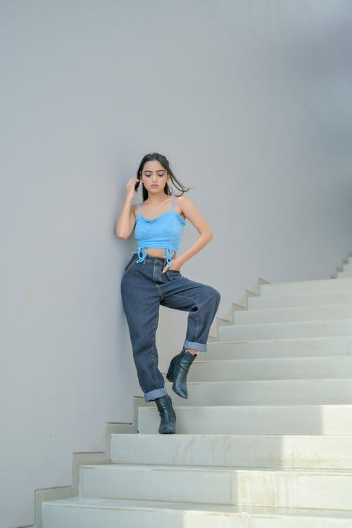 Stylish woman with hand in pocket on stairs