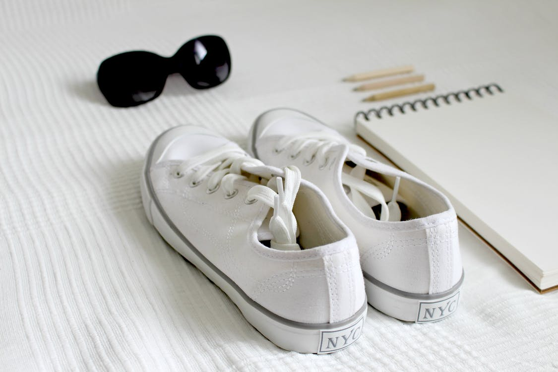 Pair Of White Nyc Low-top Sneakers Beside Notebook
