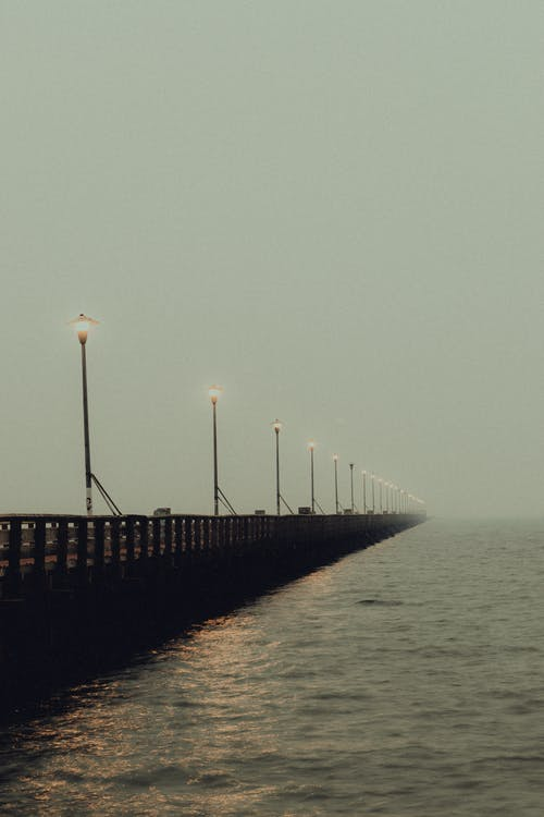 Long pier near rippling water of river on cloudy misty weather in summer