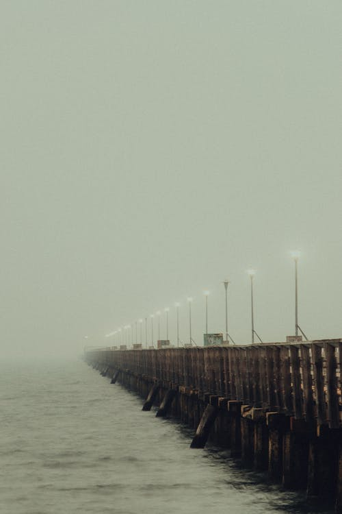 Foggy bridge with streetlights glowing in fog above rippling water on gloomy cloudy gray day