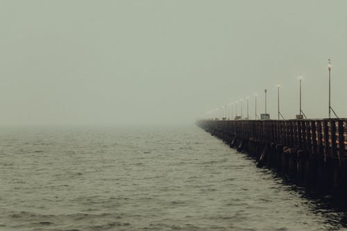 Long pier with streetlights running away above calm sea water in mist under cloudy gloomy sky