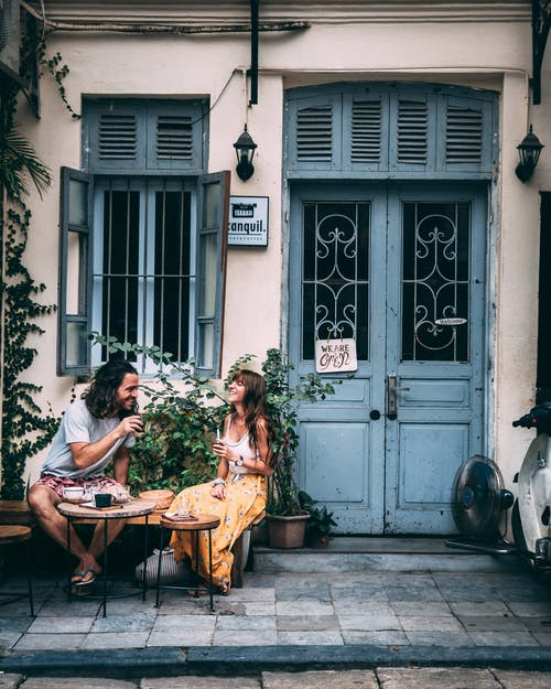 Man and Woman Sitting on Bench Beside a Blue Front Door