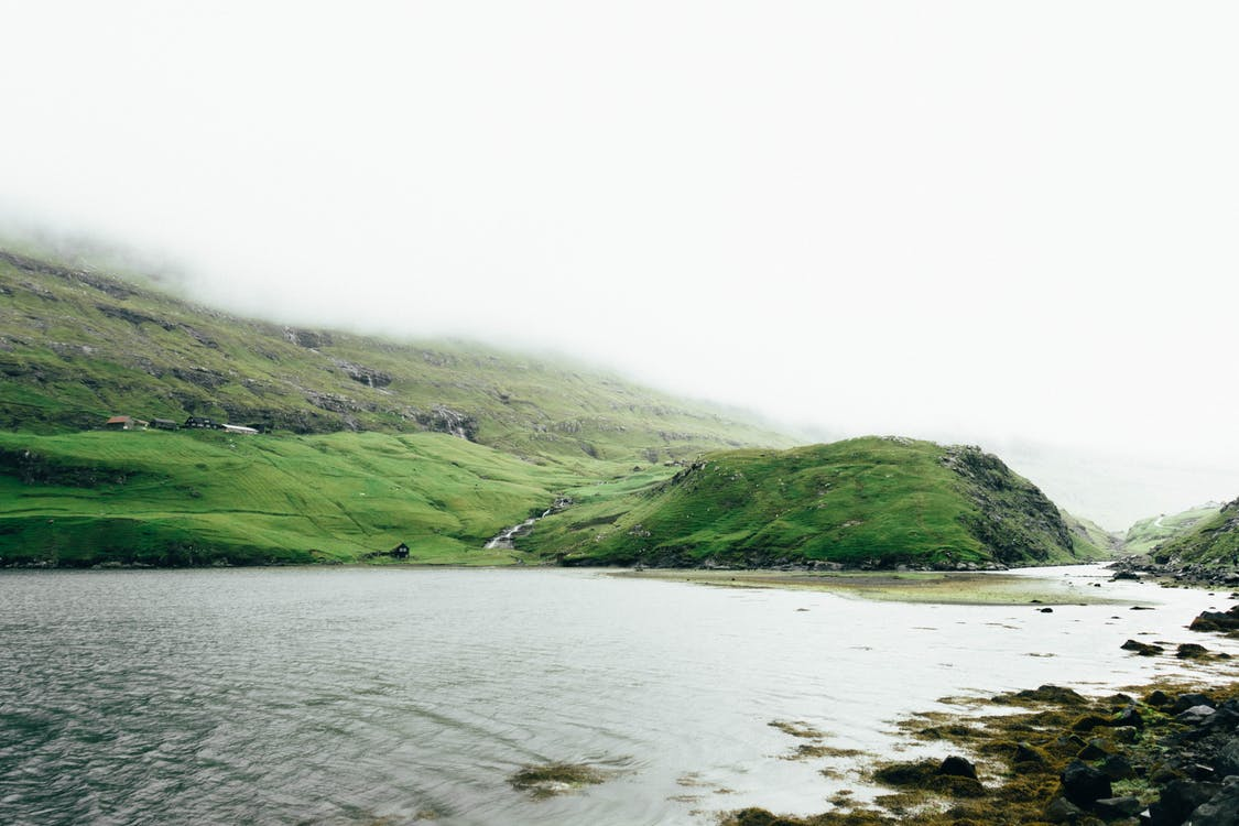 Green Grass Covered Mountain Beside Body of Water