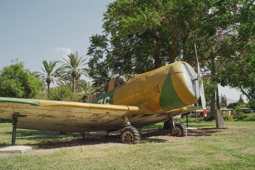 Yellow and White Boat on Green Grass Field