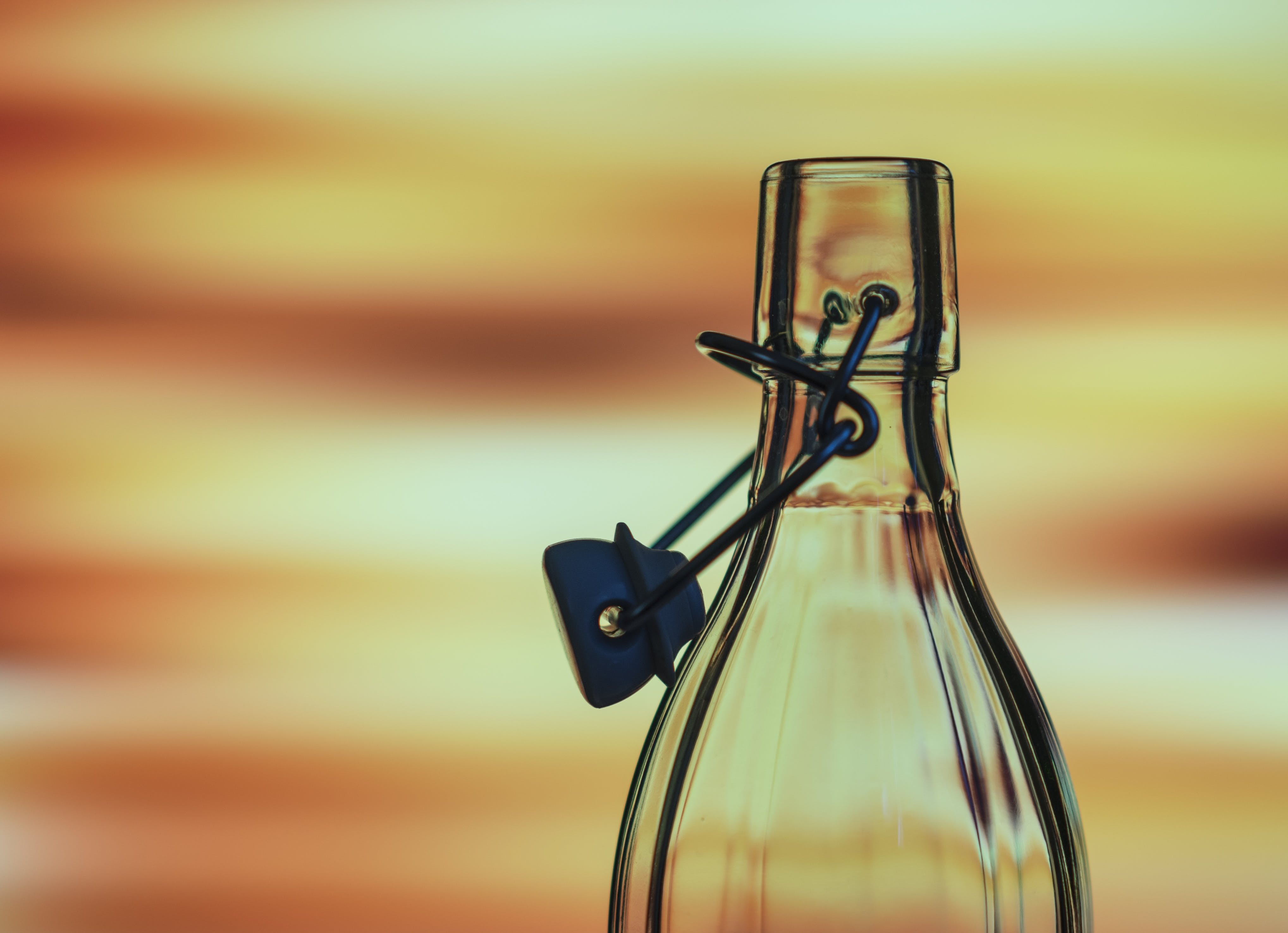 Selective Focus Photography Clear Swing Top Glass Bottle