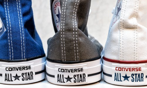 Three Unpaired Black, Blue, and White Converse All Star Sneakers on White Surface