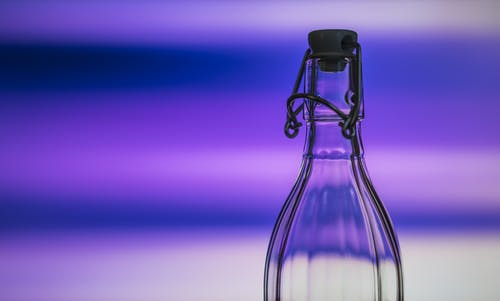 Shallow Photo of Clear Glass Bottle