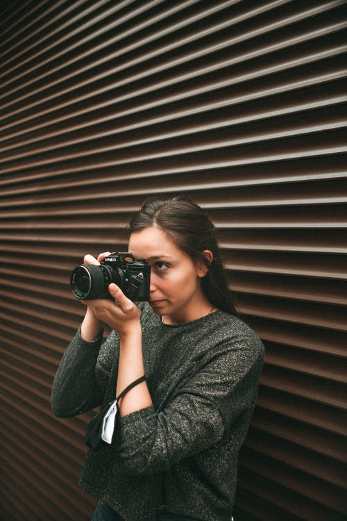 Woman in Gray Long Sleeve Shirt Holding Black Dslr Camera