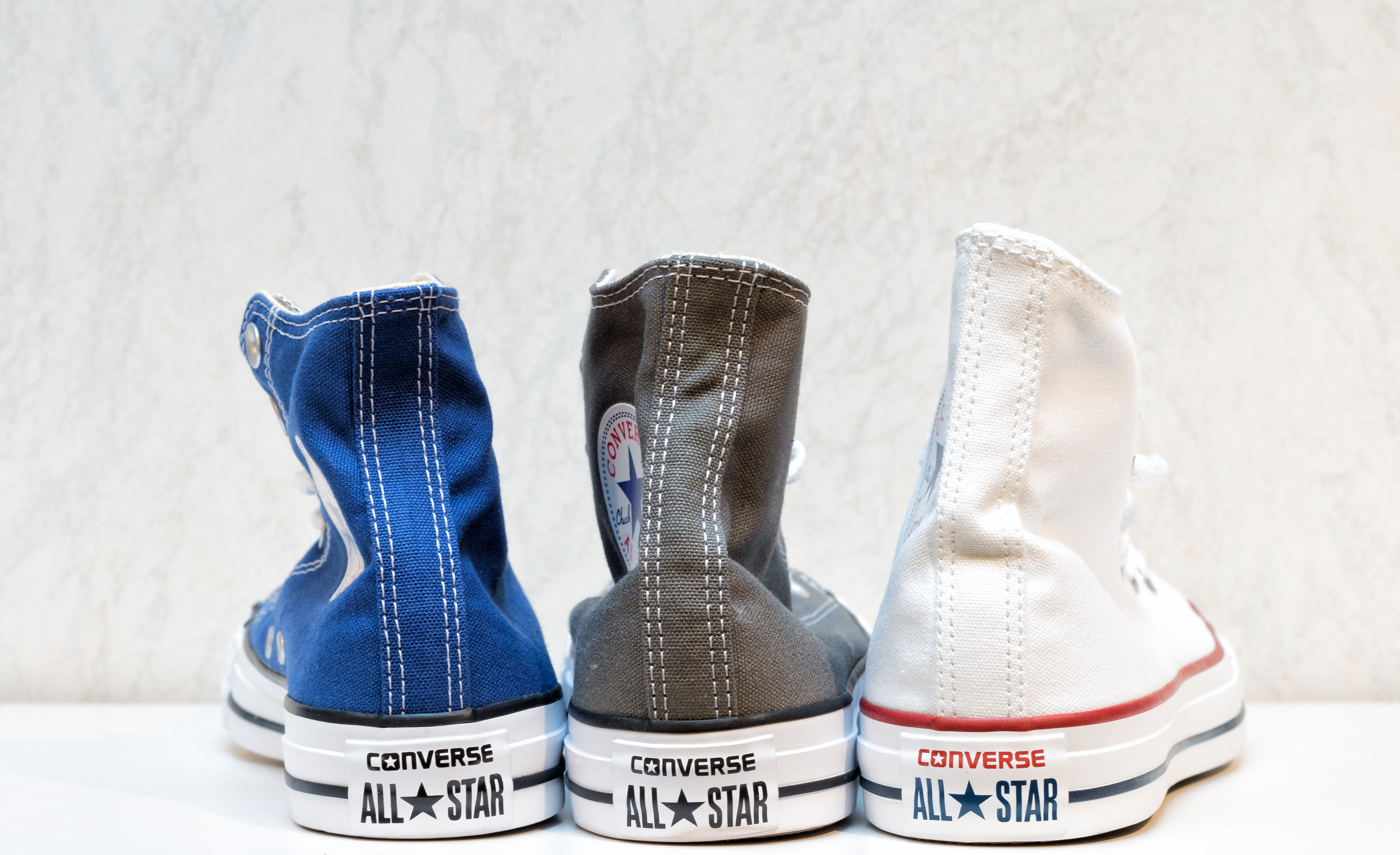 Unpaired White, Blue, and Brown Converse All-star High-top Sneakers