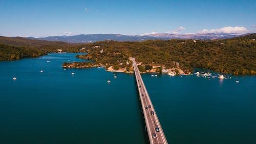 Gray Concrete Bridge over Blue Sea Under Blue Sky