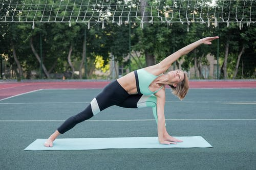 Slim barefoot female in sportswear standing in Utthita Parsvakonasana pose while practicing yoga on mat on sports ground and looking up