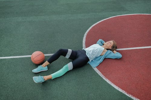 From above of young content female athlete in stylish sportswear lying on sports ground near ball after training and looking up