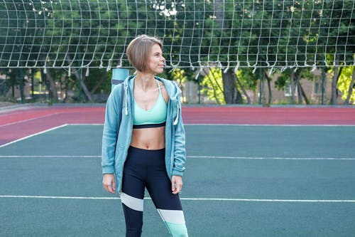 Stylish sportswoman in active wear on sports ground