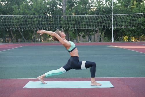 Woman Standing In Crescent Lunge Pose Sur Tapis De Yoga