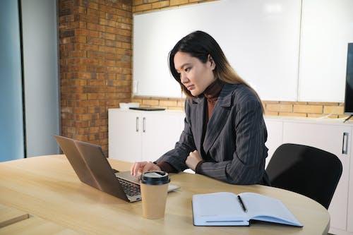 鍵入在膝上型計算機的亞裔女實業家在桌上在辦公室