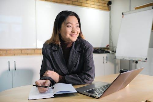 性格開朗的亞洲行政人員在桌上的筆記本電腦和日記