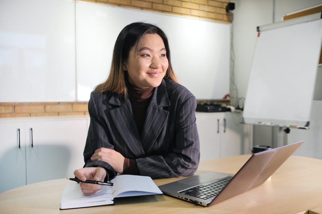 Ejecutivo Asiático Alegre En Mesa Con Portátil Y Diario