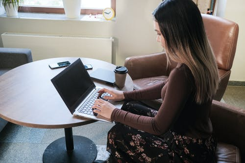 Focused young businesswoman working on laptop at table