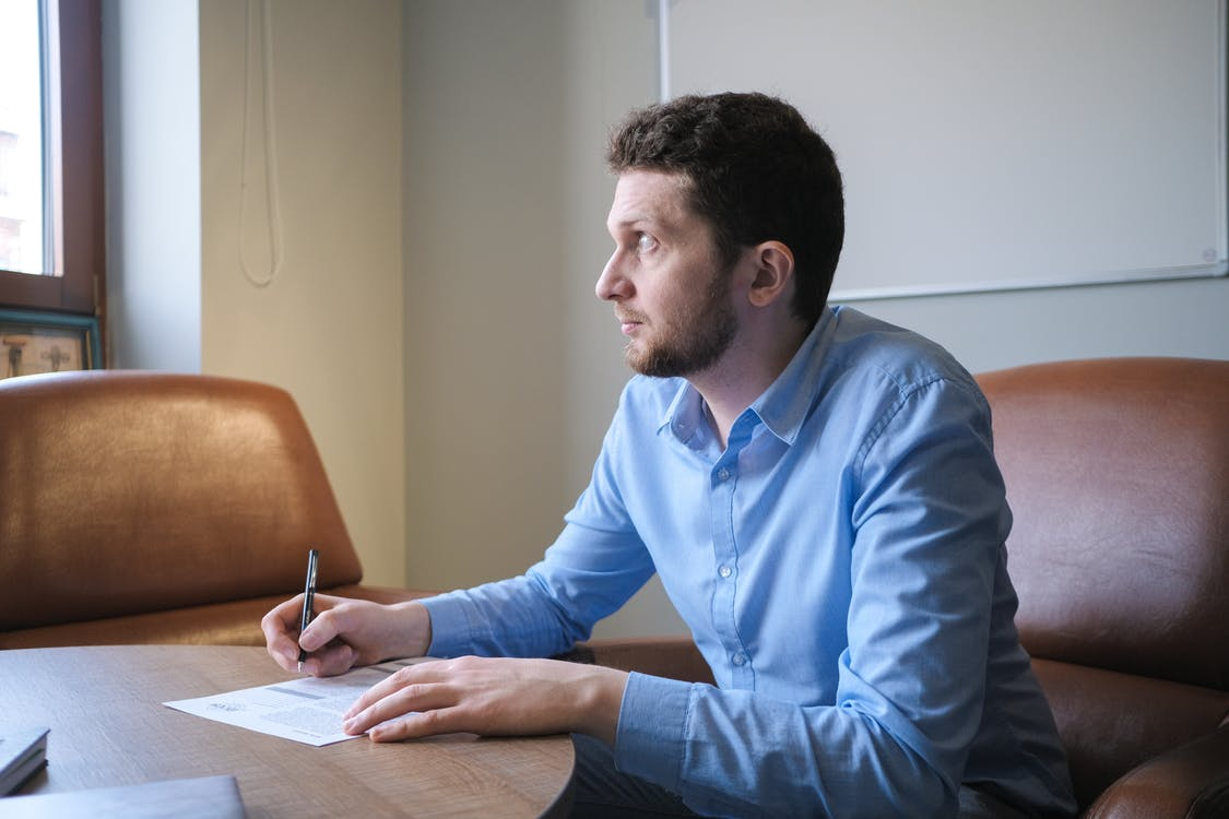 Thoughtful man thinking on business strategy and making notes