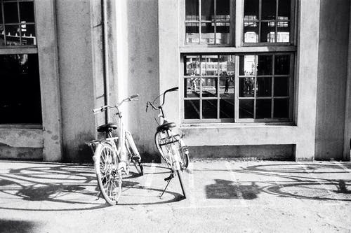 Bicycles parked on sidewalk near concrete building