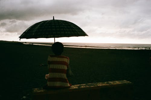 Back view of anonymous female with umbrella enjoying sea on sandy shore in cloudy day