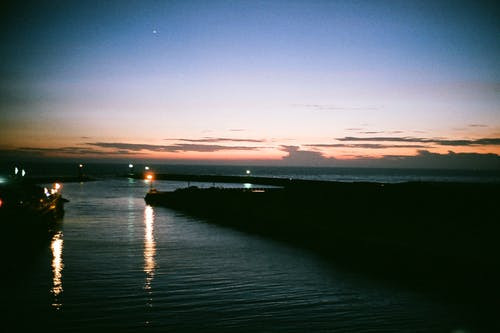 Silhouette of embankment washed by rippling sea with lights reflecting on water surface at sunset