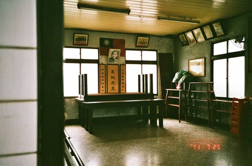 Interior of community hall with wooden furniture and Asian hieroglyphs and pictures on walls