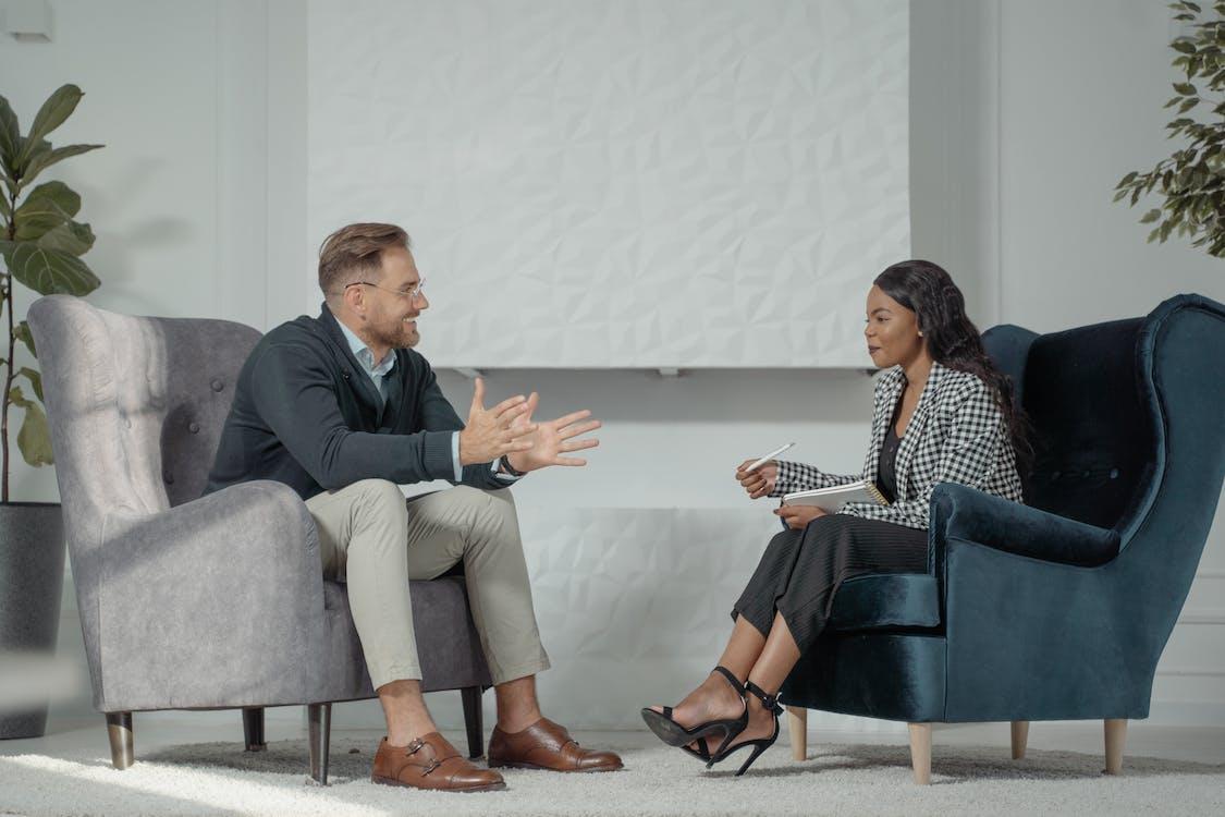 Man and Woman Sitting on Gray Sofa