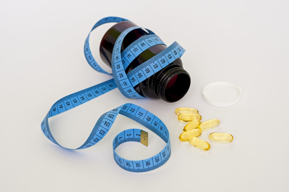 Blue Tape Measure Wrapping Black Medication Pill Bottle With White Cap
