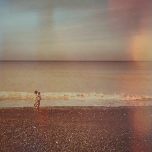 Photo of Mother And Child Standing On Seashore