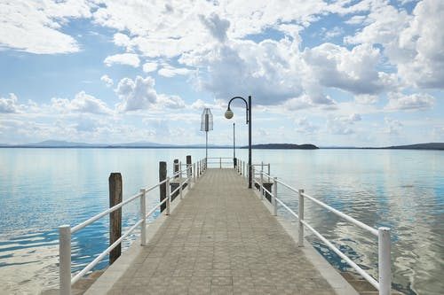 Brown Wooden Dock on Sea Under White Clouds and Blue Sky