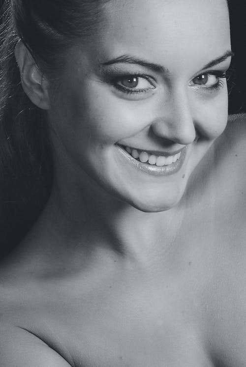 A Smiling Woman in Grayscale Photography