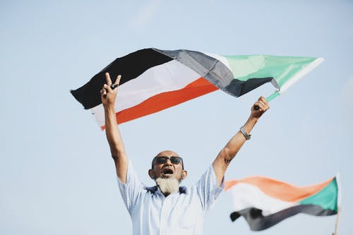 Man in Button Up Shirt Waving Sudanese Flag in Victory