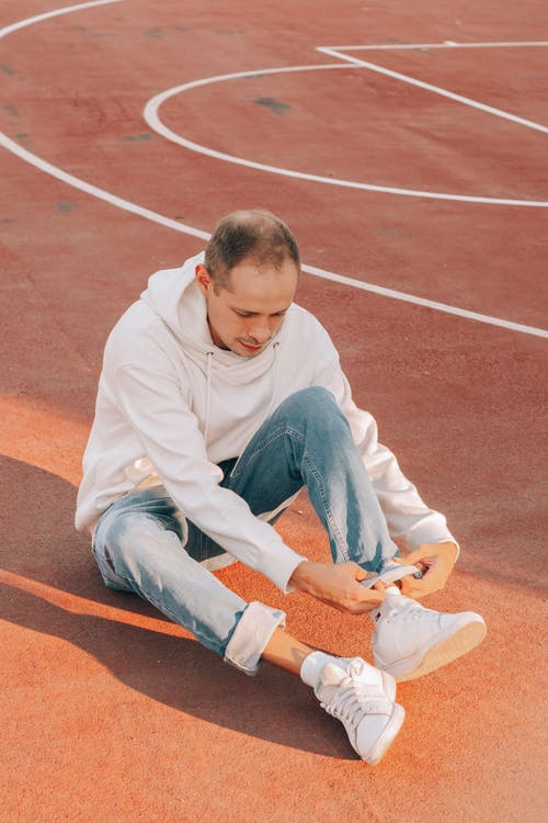 Trendy man rolling up jeans on sports ground