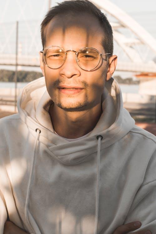 Crop stylish man in eyeglasses and hoodie in town