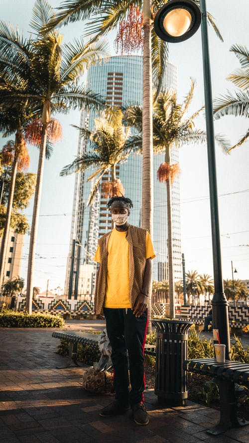 Full length of unrecognizable young black male tourist in casual outfit and face mask standing on paved alley in park near tall palms and contemporary building
