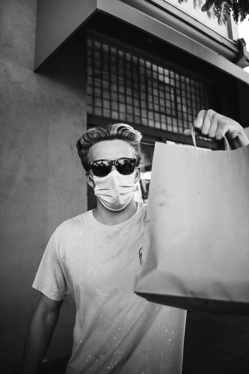 Unrecognizable young stylish male in sunglasses and medical mask demonstrating paper bags after shopping on sunny day