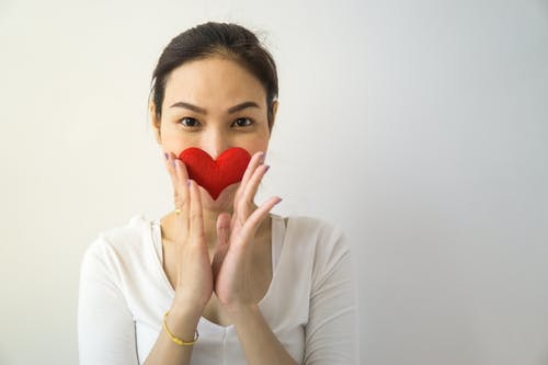 Unrecognizable female looking at camera while standing on white background with small handmade heart in hands covering mouth in room