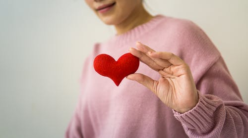 Content unrecognizable female wearing pink sweater standing on white background with small handmade heart in hand in light room inside